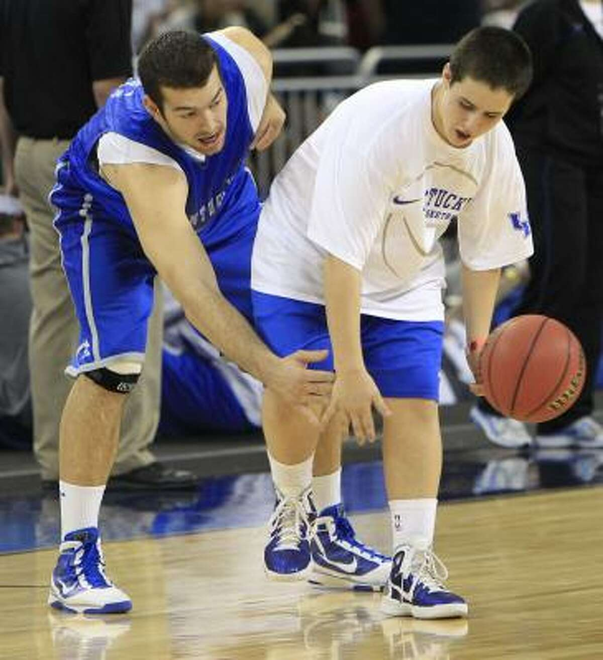 Kentucky forward Josh Harrellson, left, reaches out to steal the ball from Brad Calipari.