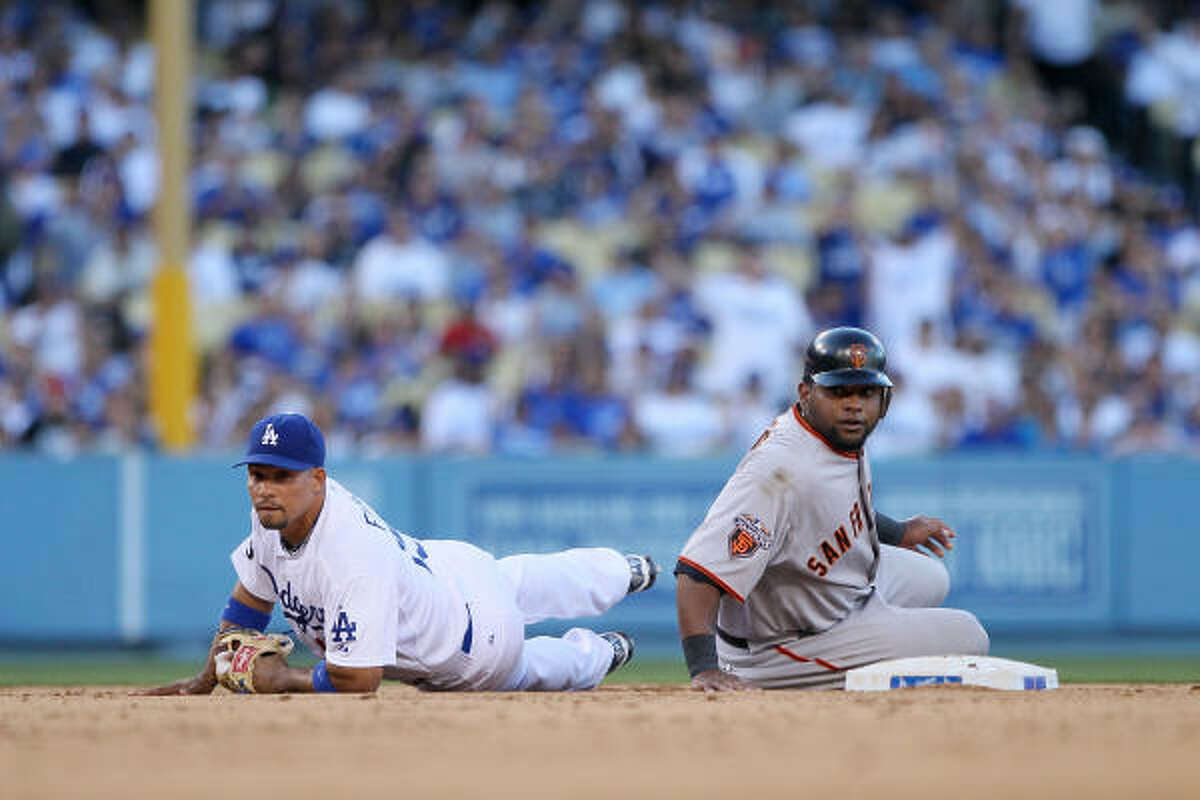 Pablo Sandoval of the San Francisco Giants looks after being tagged out by Rafael Furcal of the Los Angeles Dodgers on a sacrifice bunt attempt by Tim Lincecum.