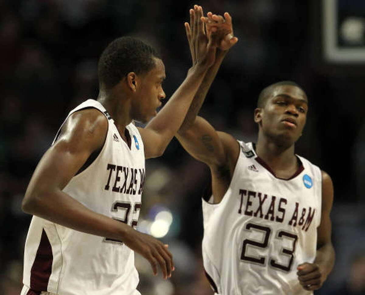 Texas A&M's Khris Middleton (22) celebrates with teammate Naji Hibbert after sinking a 3-pointer at the end of the first half.
