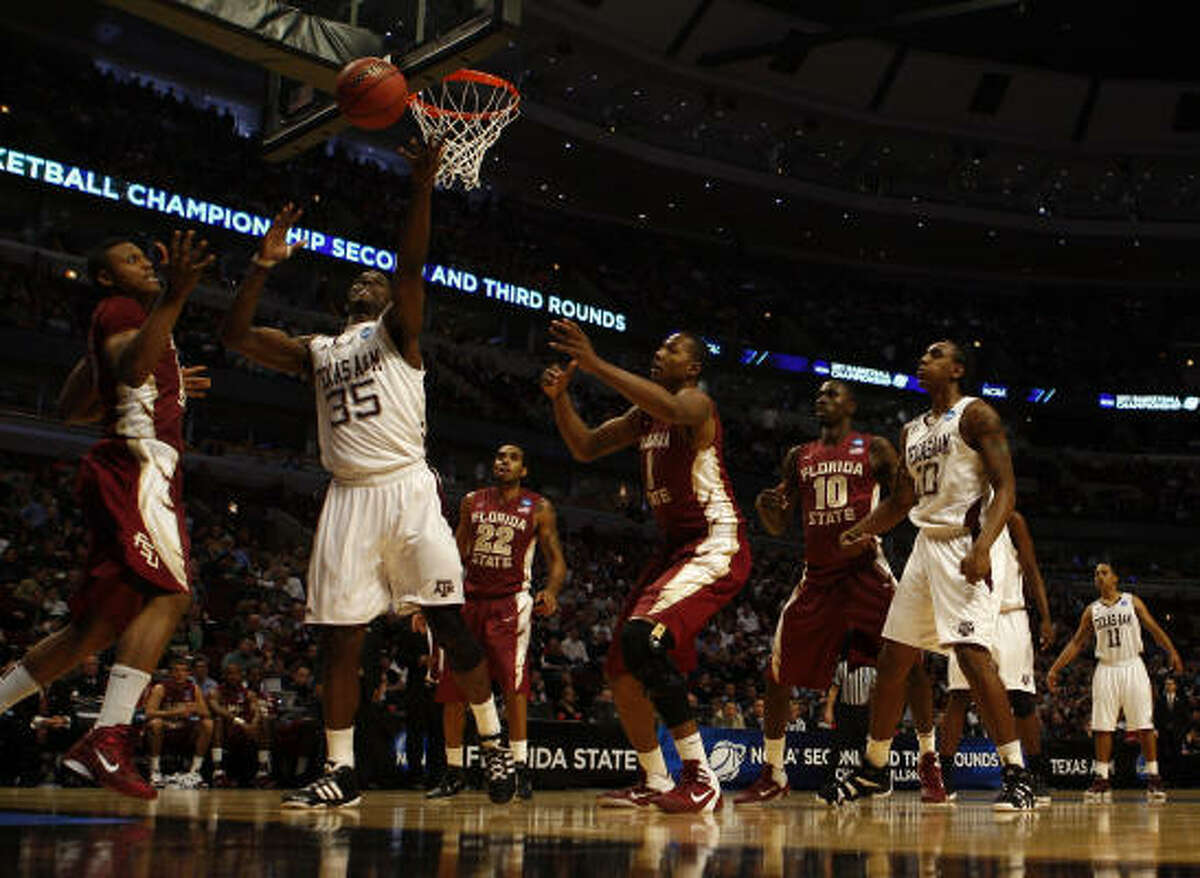 Texas A&M's Ray Turner corrals a loose ball in front of Florida State's Terrance Shannon, left, and Xavier Gibson.