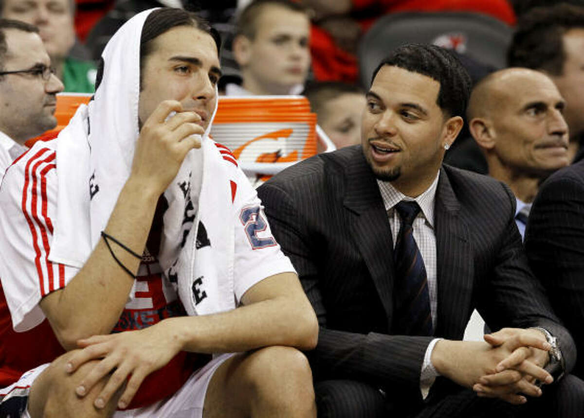Nets point guard Deron Williams, right, out with an injured wrist, talks with teammate Sasha Vujacic on the bench.