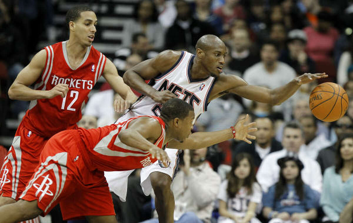Rockets guard Kyle Lowry, bottom, and Nets forward Travis Outlaw, top right, reach for the ball.