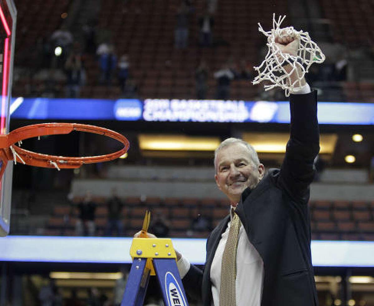 Connecticut Huskies head coach Jim Calhoun smiles after cutting down the net after their winning the NCAA West Regional Final.