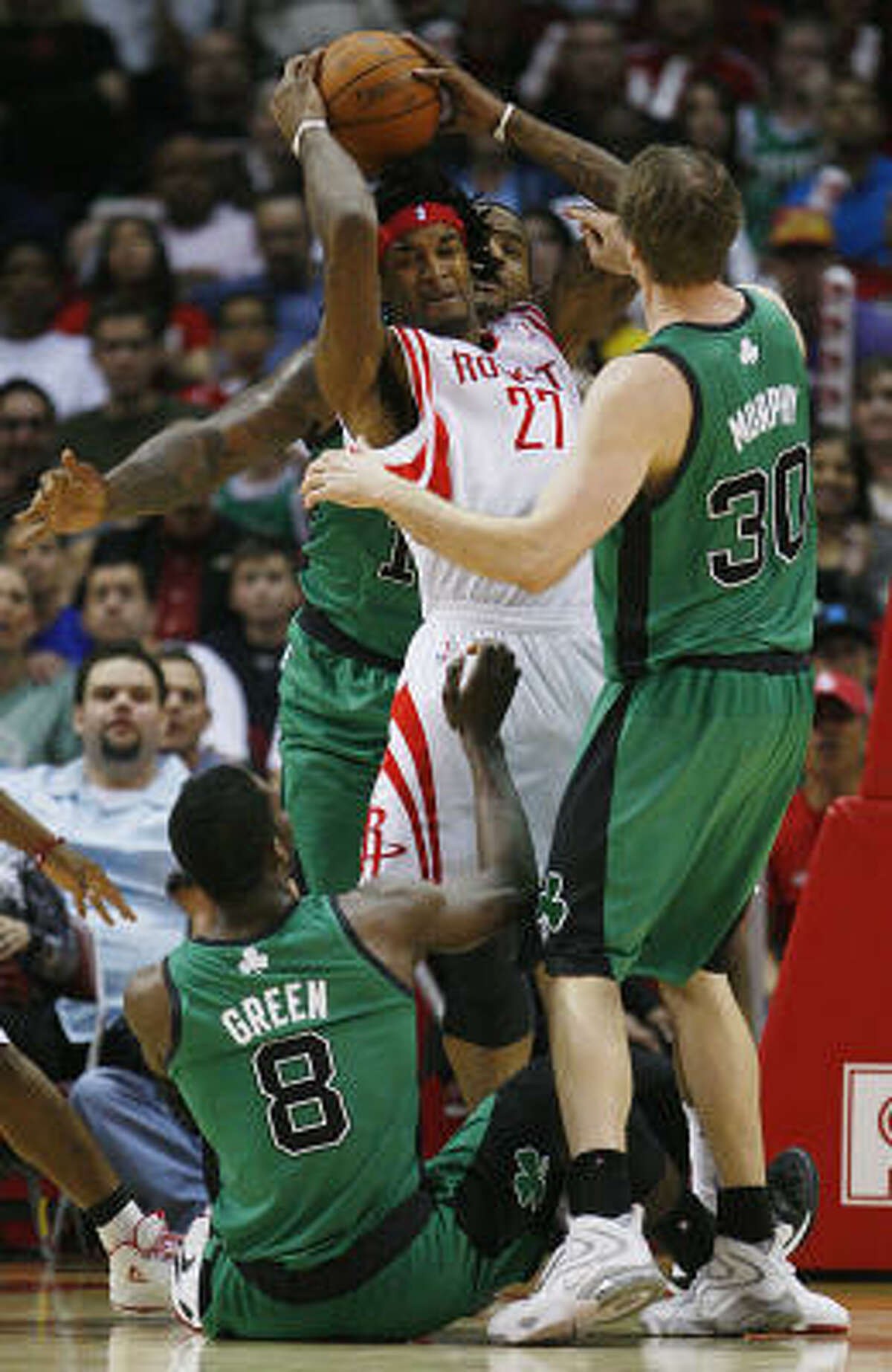 Rockets forward Jordan Hill is surrounded by Celtics forwards Jeff Green, rear, and Troy Murphy during the first half.