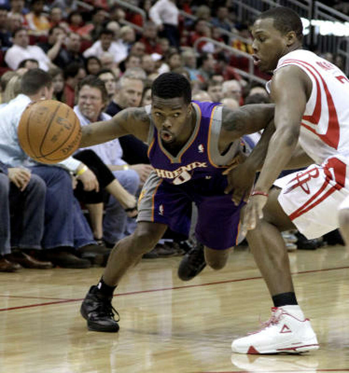 Suns' Aaron Brooks (0) drives around Rockets' Kyle Lowry, right.
