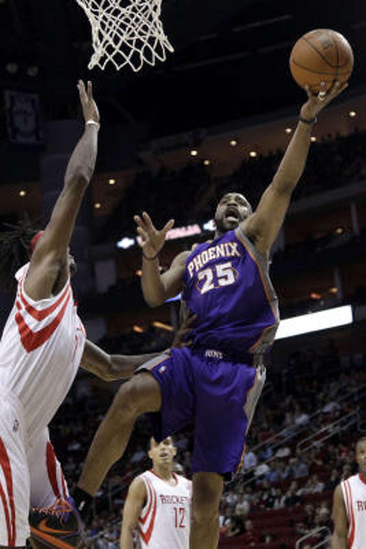 Suns' Vince Carter (25) goes up for a shot as Houston Rockets' Jordan Hill, left, defends.