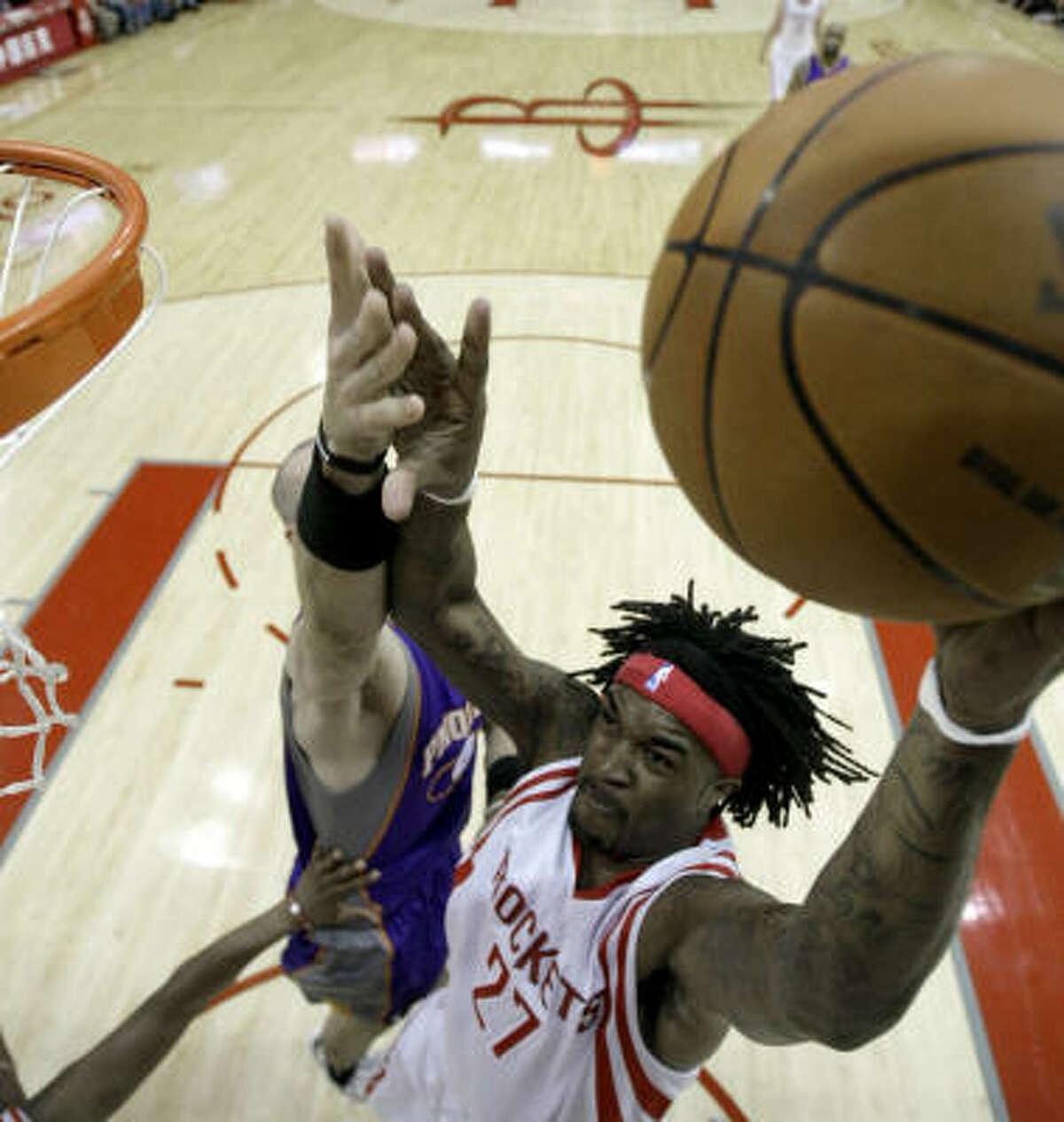 Rockets' Jordan Hill (27) goes up for a shot as Suns' Marcin Gortat, left, defends.