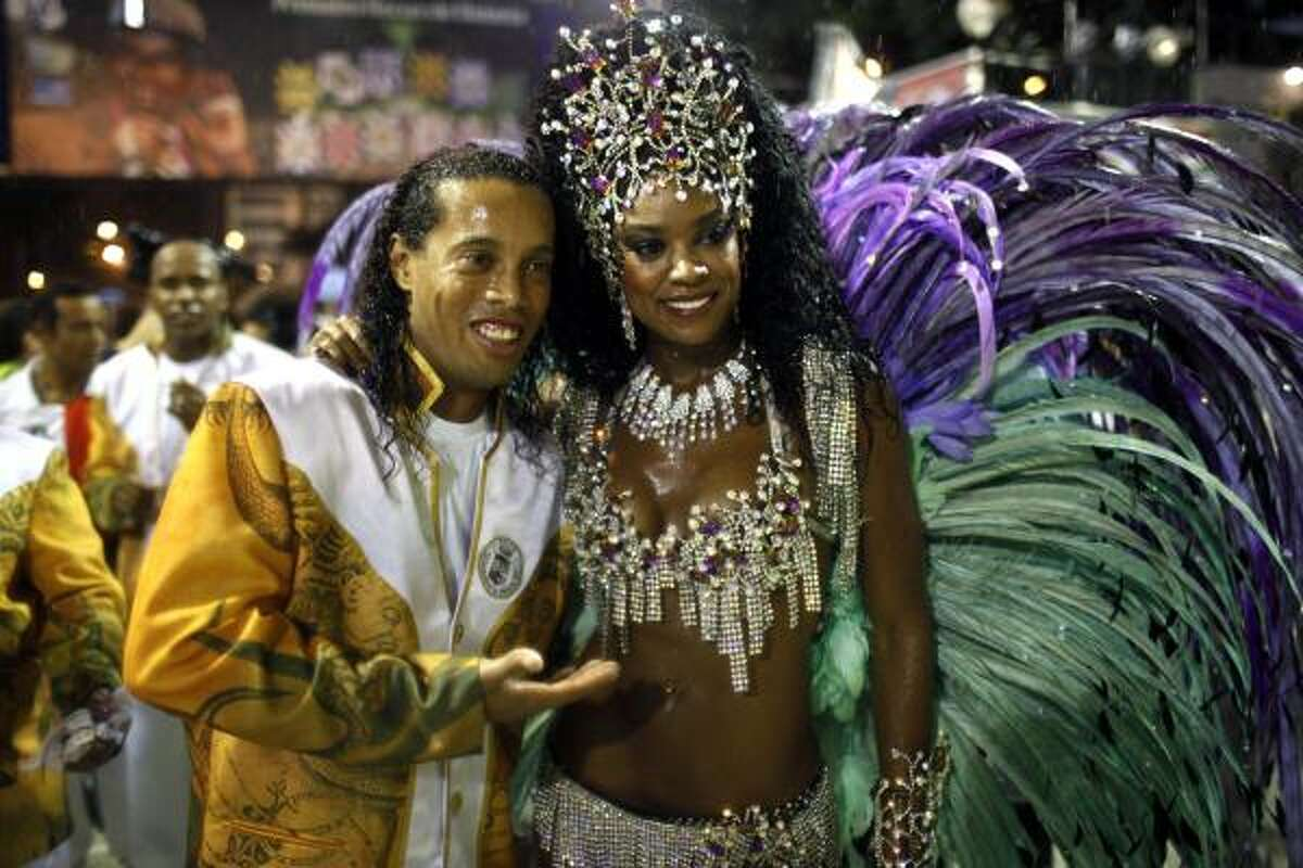 Brazilian soccer player Ronaldinho, left, embraces Cris Vianna, queen of the drums section of the Grande Rio samba school, while posing for pictures during carnival celebrations at the Sambadrome in Rio de Janeiro, Brazil.
