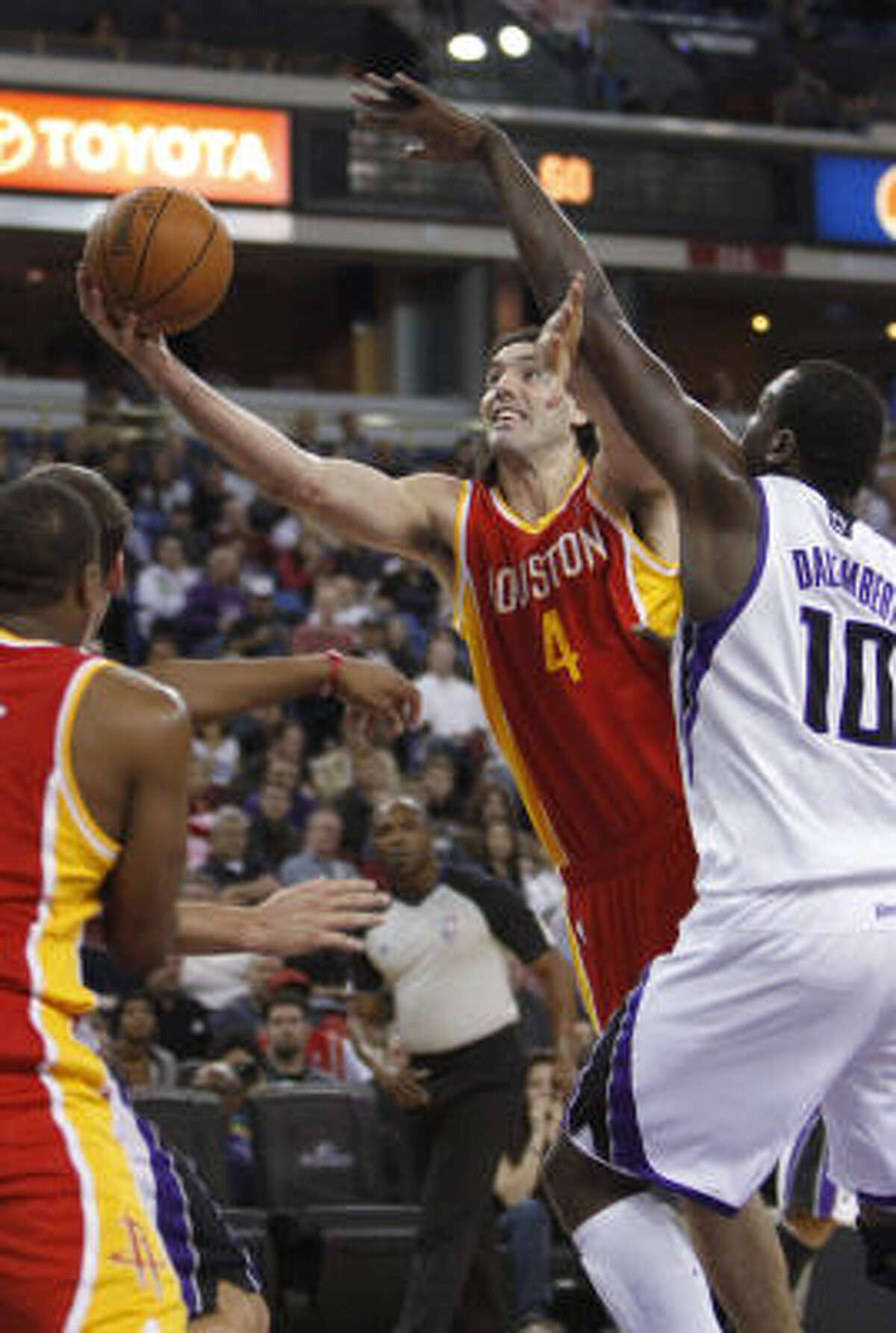 Rockets forward Luis Scola goes to the basket past Kings center Samuel Dalembert, right.