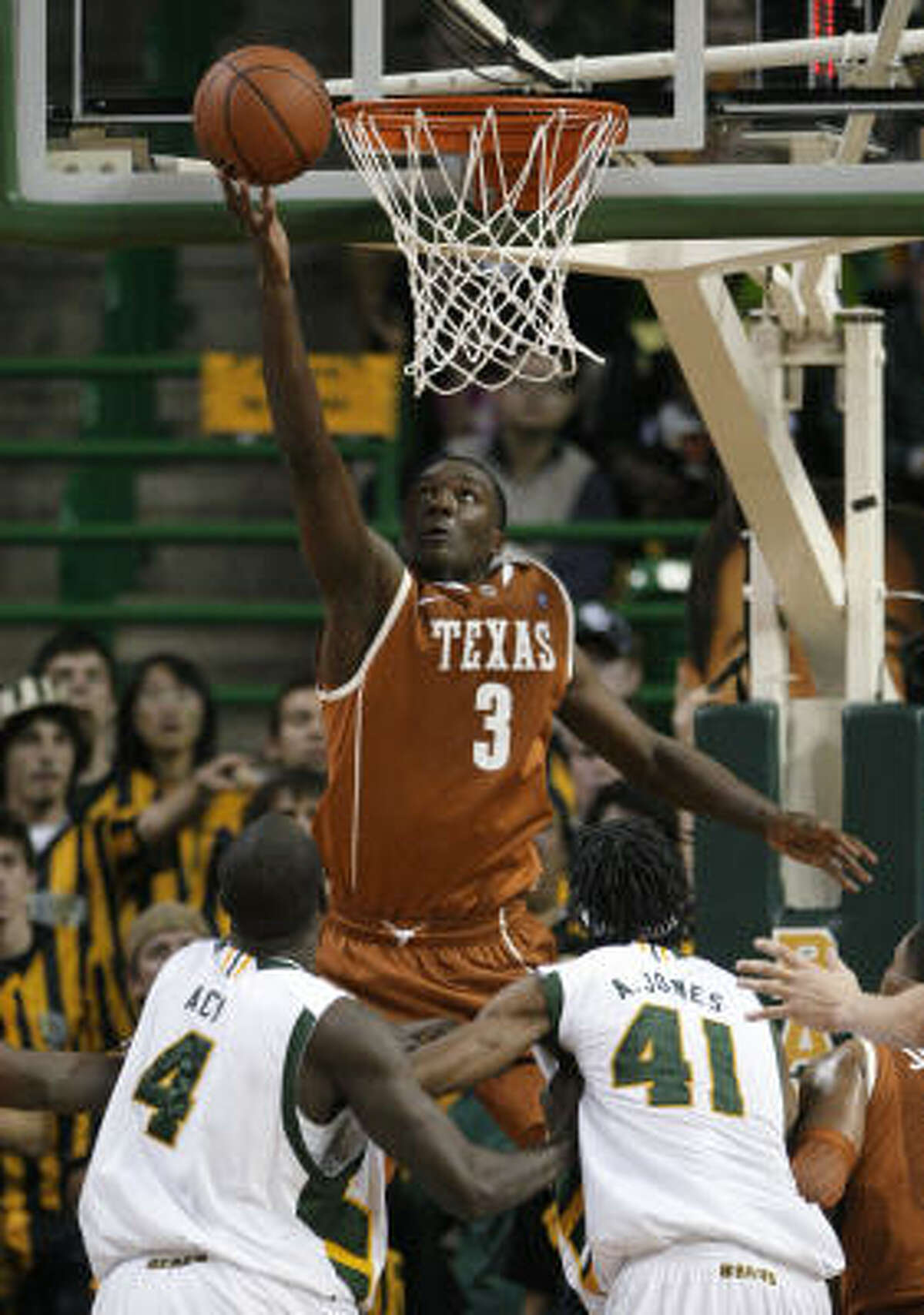 Texas' Jordan Hamilton (3) attempts a layup over Baylor forwards Quincy Acy (4) and Anthony Jones in the second half.