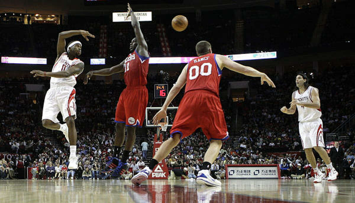 Rockets guard Aaron Brooks, left, passes the ball to teammate Luis Scola, right, during the fourth quarter.