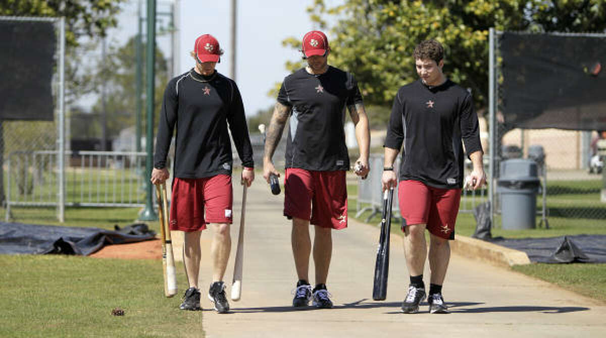 Catcher J.R. Towles, left, Brian Dopirak, center, and Brett Wallace, right, walk back to the clubhouse after hitting in the batting cages.