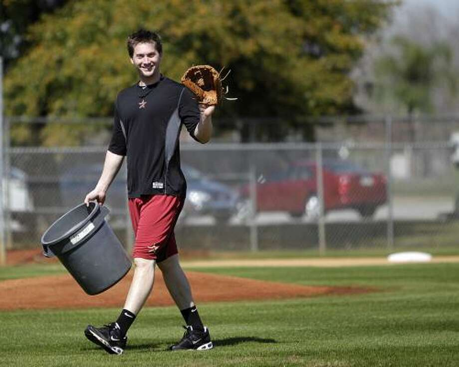 Chris Johnson waves to the camera as he carries a bucket of balls on the practice field. Photo: Karen Warren, Chronicle