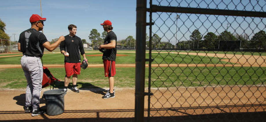 First base coach Bobby Meacham, left, stands on a field with Chris Johnson, center, and Brian Dopirak as they prepare to do a light workout. Photo: Karen Warren, Chronicle