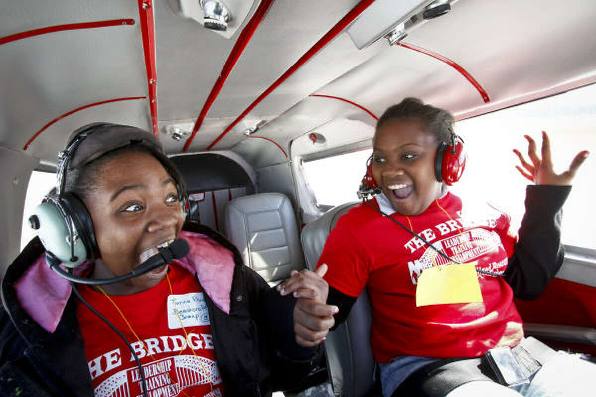 Tianna Rhodes, 11, and Tylandria Harrison, 11, react to what is there first flight ever as the Piper Cherokee Six aircraft, flown by Chris Prause, takes off from the runway at the Houston Southwest Airport. Forty kids from the troubled Haverstock apartment complex were bussed to the Texas Taildraggers flight school where they took a 20 minute ride in the sky in the hopes they see life beyond the gates of their home. The event was organized by Wendall Champion, a volunteer trying to change Haverstock Hills Apartments. Chad Johnson, part owner of Texas Taildraggers flight school, volunteered the facility for the day.
