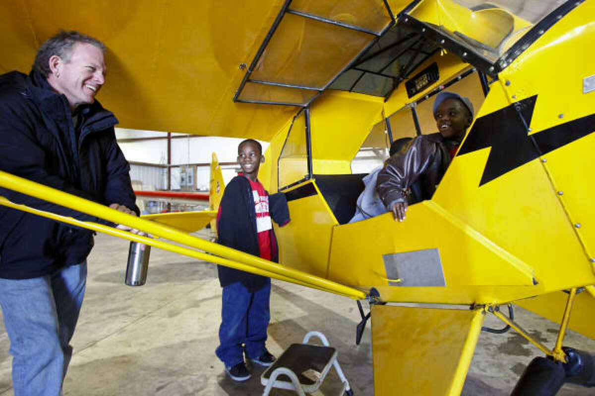Benjamin Utley, 10,. and Cameron Griffin, 10, listen as pilot Jeff Thomsen tells them about the Piper J3 Cub aircraft in the Texas Taildraggers hangar at the Houston Southwest Airport.