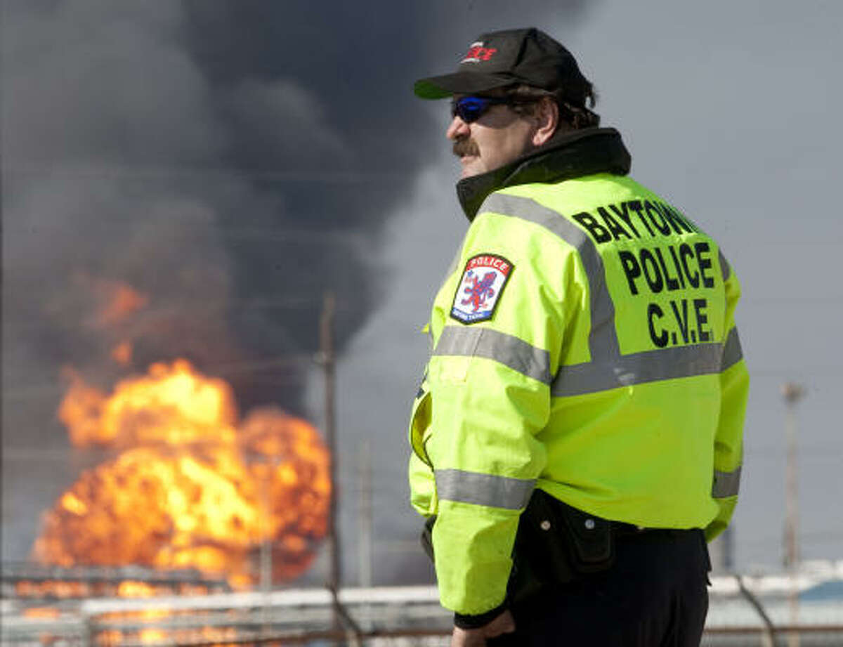 A Baytown police officer diverts the flow of traffic at Sun Oil Rd and Main in Mont Belvieu, Texas, on Tuesday, Feb. 8, 2011 as flames and smoke rise from an explosion at Enterprise Products Partners' natural gas complex.