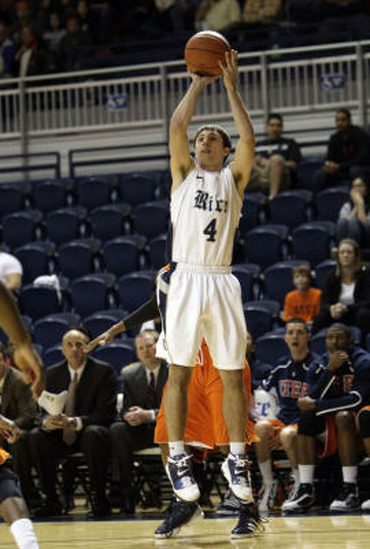 Rice's Connor Frizzelle (4) puts up a jumper from the baseline corner.