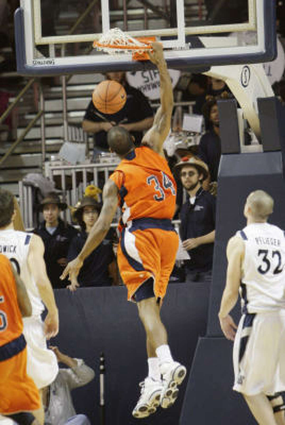 UTEP's Jeremy Williams (34) dunks over Rice's Cory Pflieger (32).