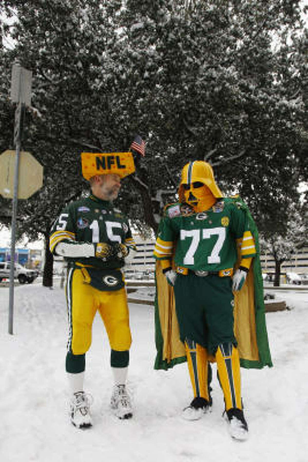 Green Bay Packers fans Steve Tate, left, and Adam Dillman wait to cross a snowy street near the Super Bowl Media Center.