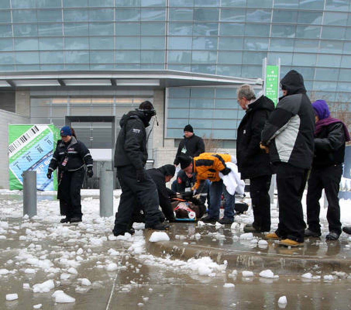 Medical personnel tend to a person injured by ice that fell off Cowboys Stadium.