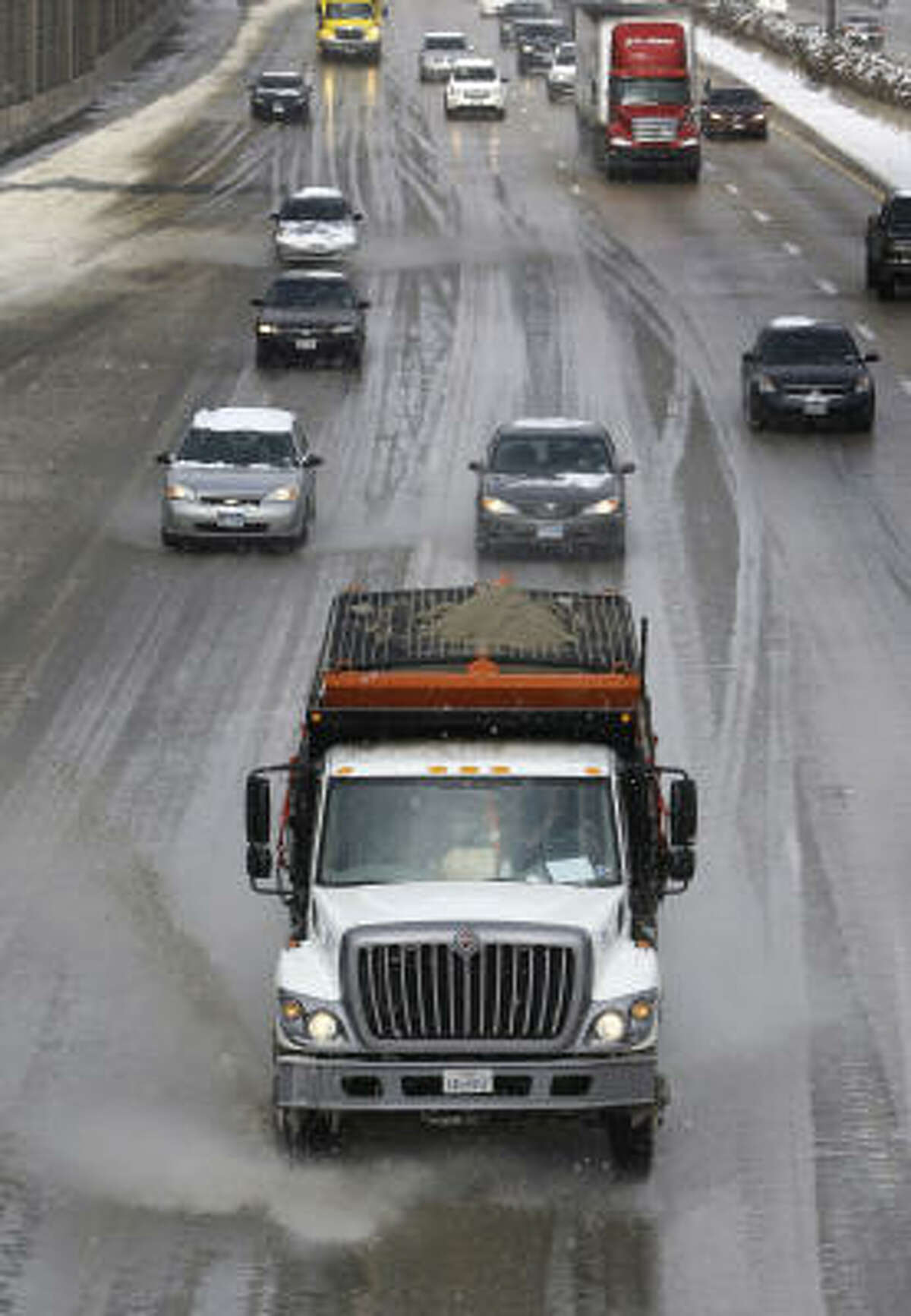 A state truck, foreground, drives southbound on Highway 75 with a load of sand and melting agent, as it and others drive through slush on Friday.