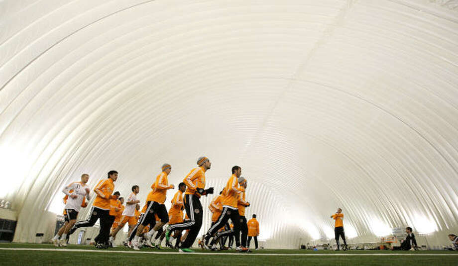 Dynamo players run before the start of Wednesday's practice in the Methodist Training Facility across from Reliant Stadium. Their practice was moved indoors to prevent any weather-related injuries. Photo: Karen Warren, Chronicle