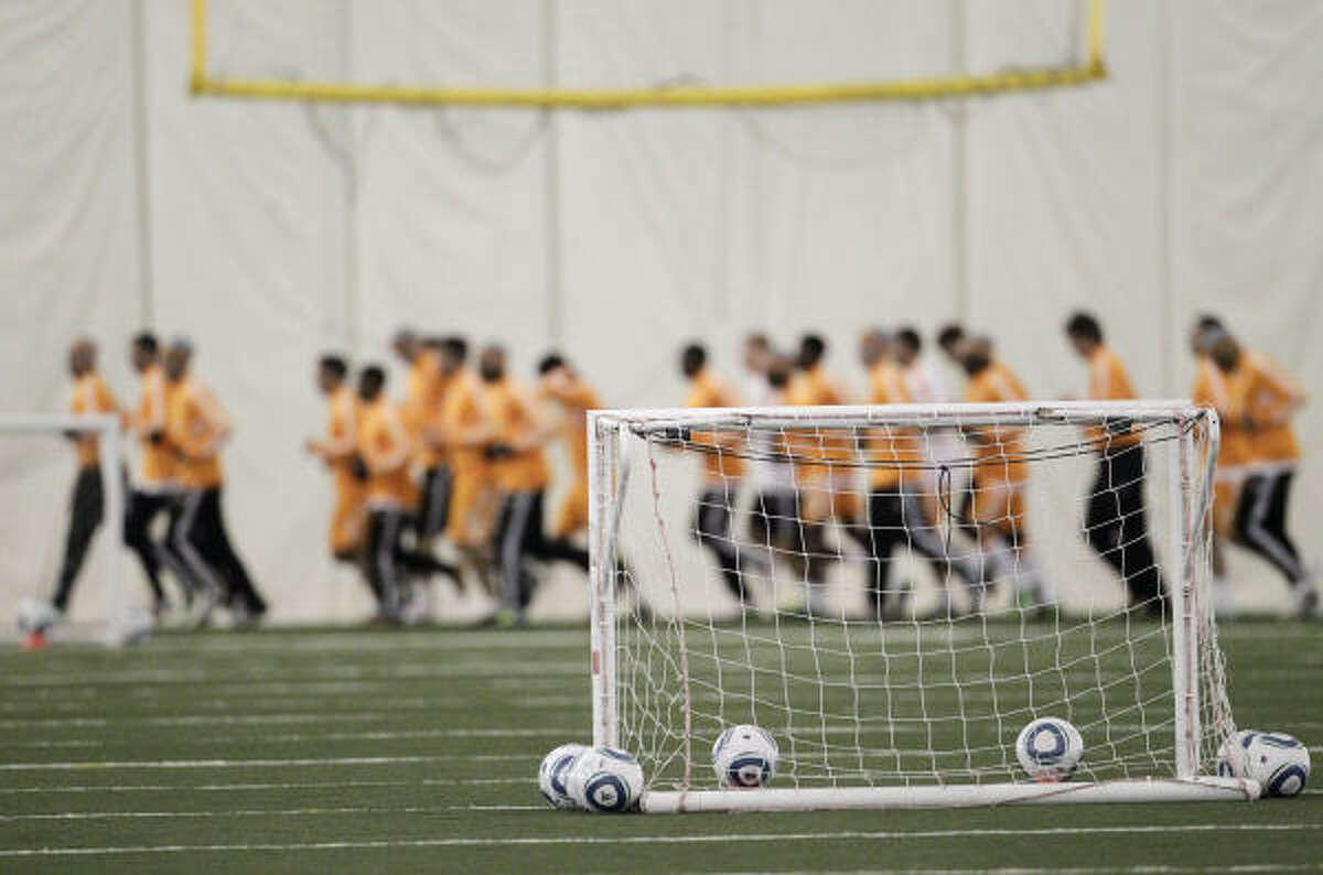 Dynamo players warm up by running before the start of practice Wednesday.