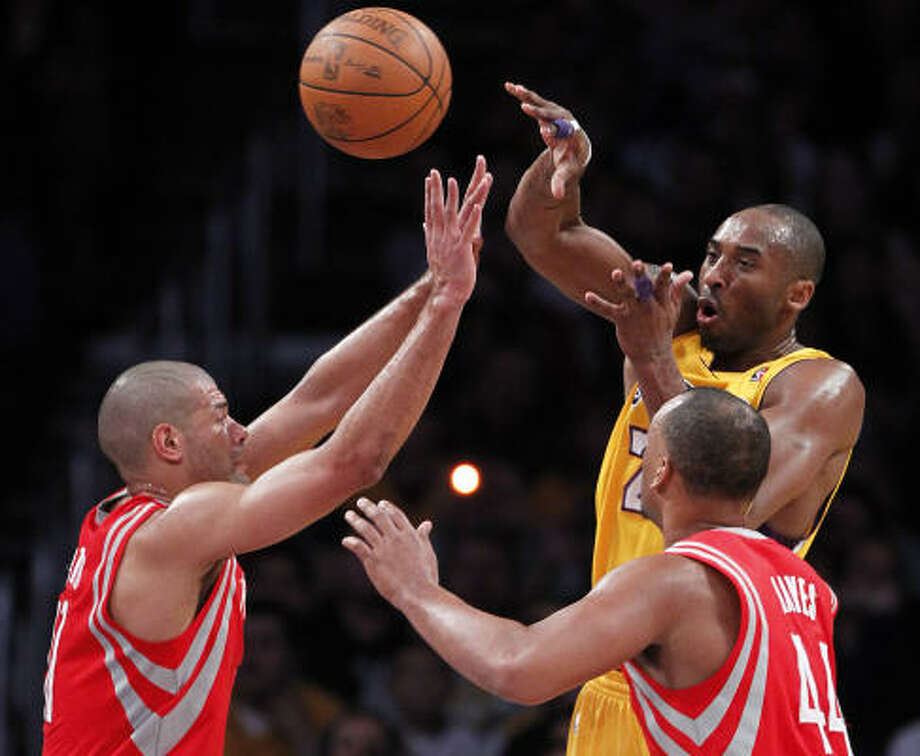 Los Angeles Lakers guard Kobe Bryant, right, passes over Rockets forward Shane Battier, left, and center Chuck Hayes during the first half. Photo: Chris Carlson, AP