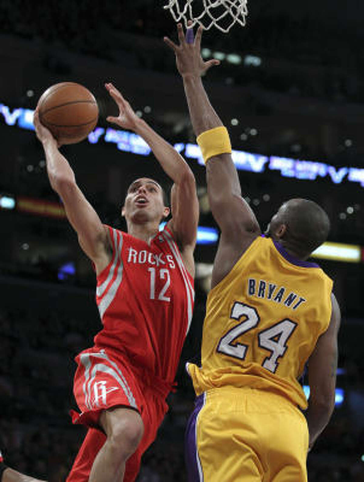 Rockets guard Kevin Martin, left, shoots around Lakers guard Kobe Bryant during the first half.
