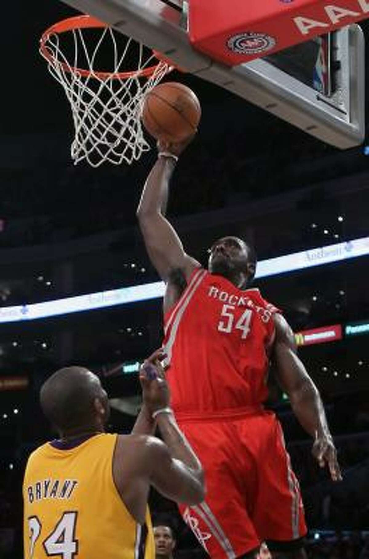 Rockets forward Patrick Patterson looks to throw one down as Lakers guard Kobe Bryant looks on.