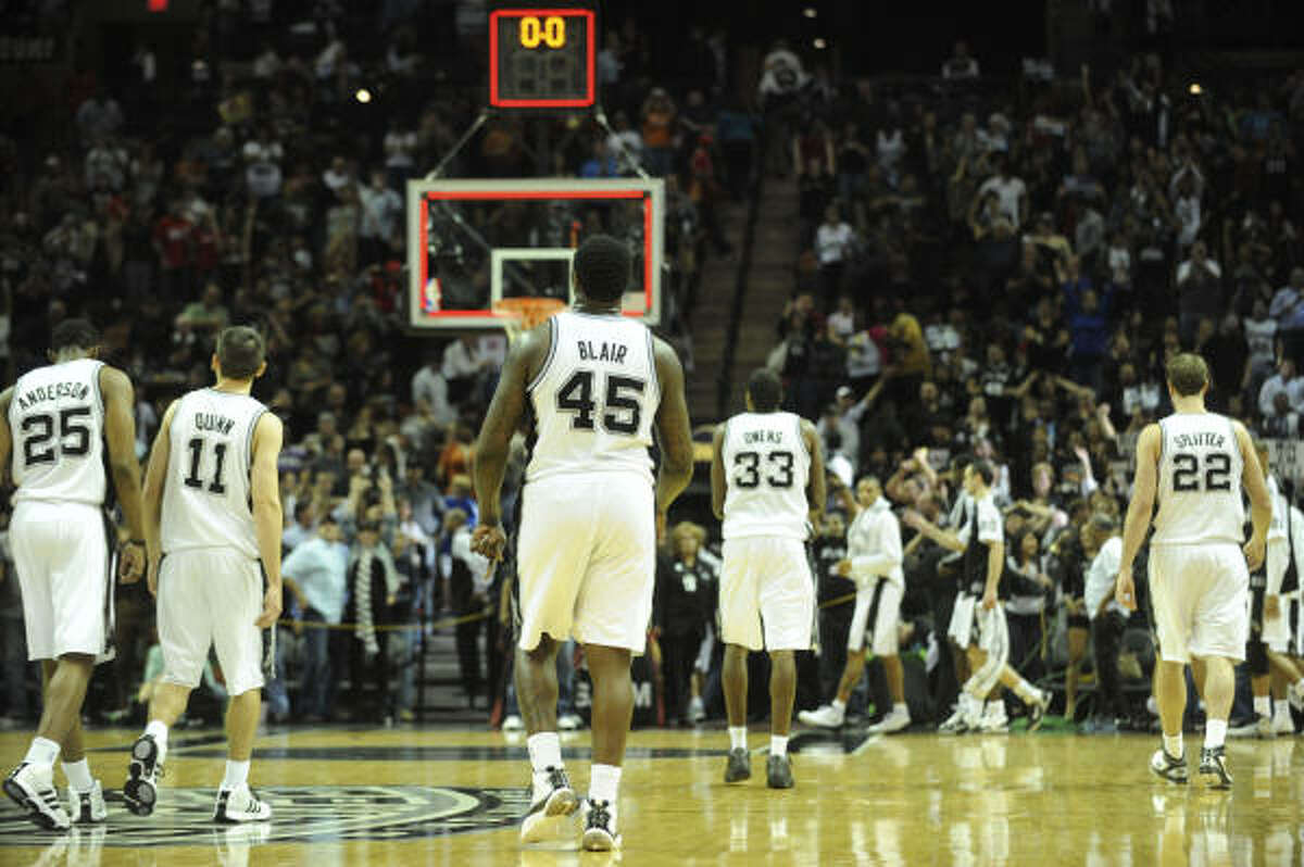 The Spurs walk off the court after defeating the Rockets.