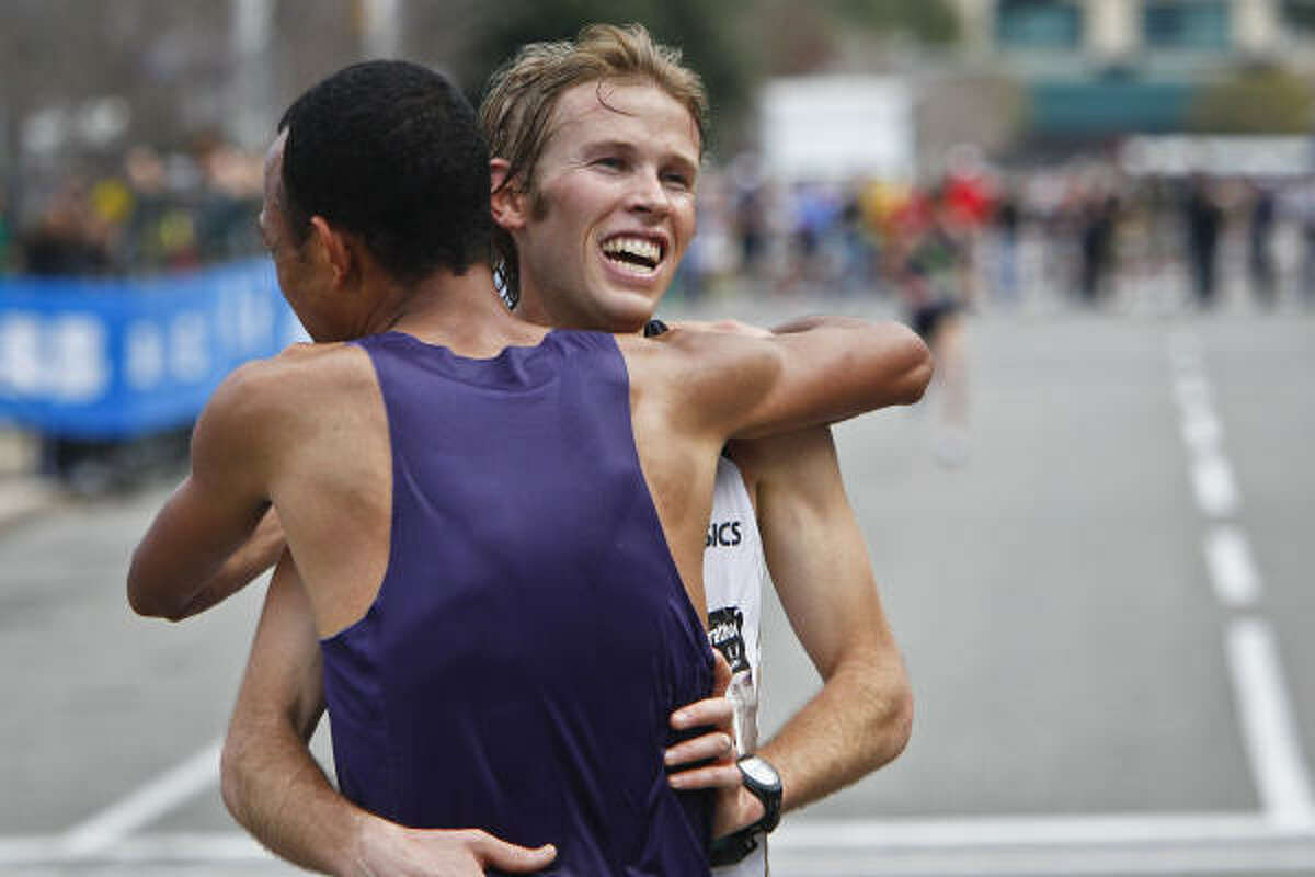 Ryan Hall (right) hugs Mo Trafeh after Hall came in second to Trafeh.