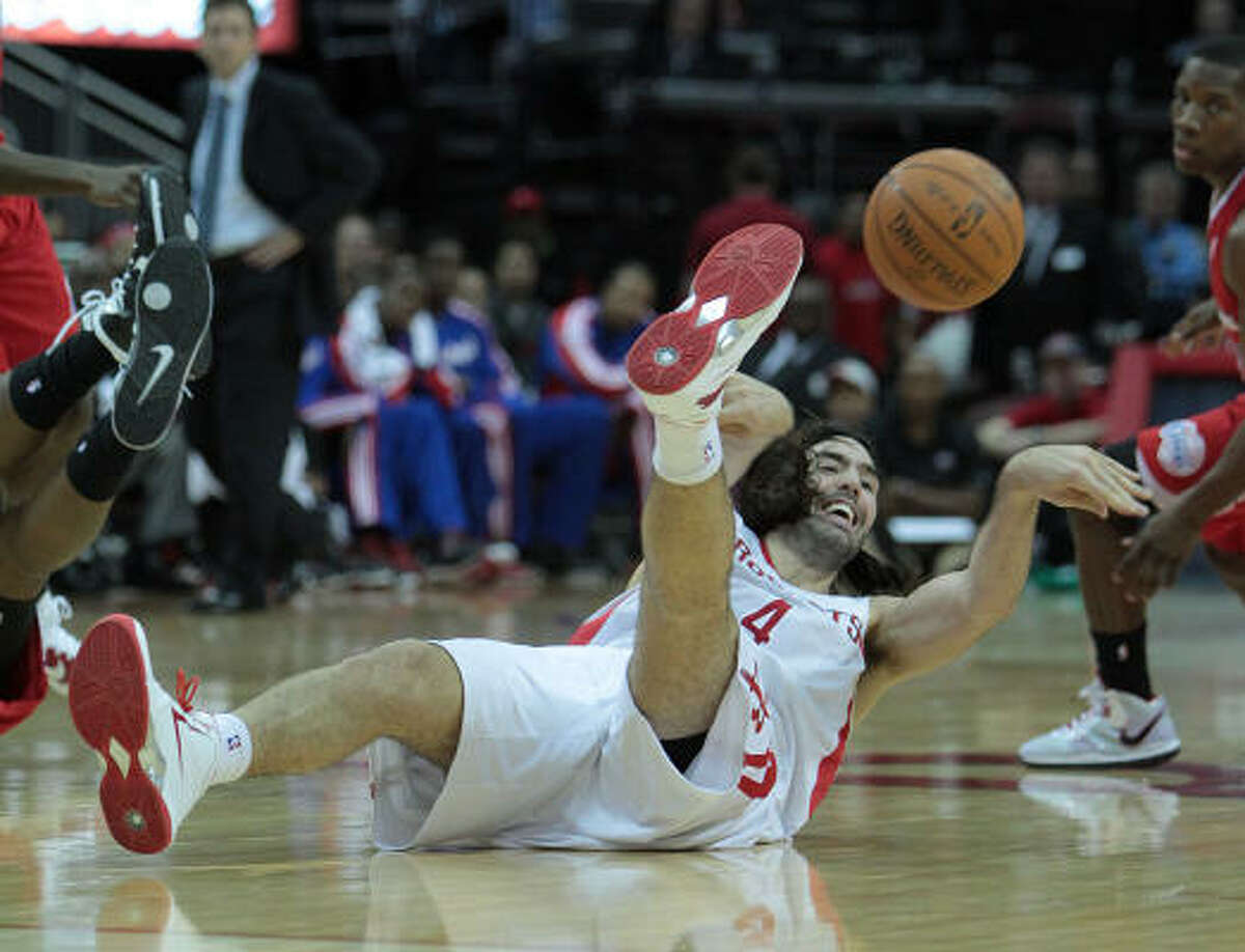 Rockets forward Luis Scola (4) hits the ground fighting for a loose ball.