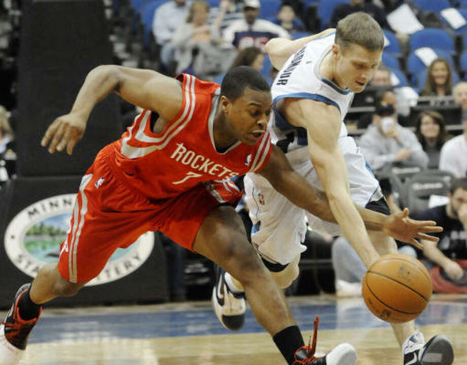 Rockets guard Kyle Lowry battles Timberwolves guard Luke Ridnour, right, for a loose ball. Photo: Jim Mone, AP