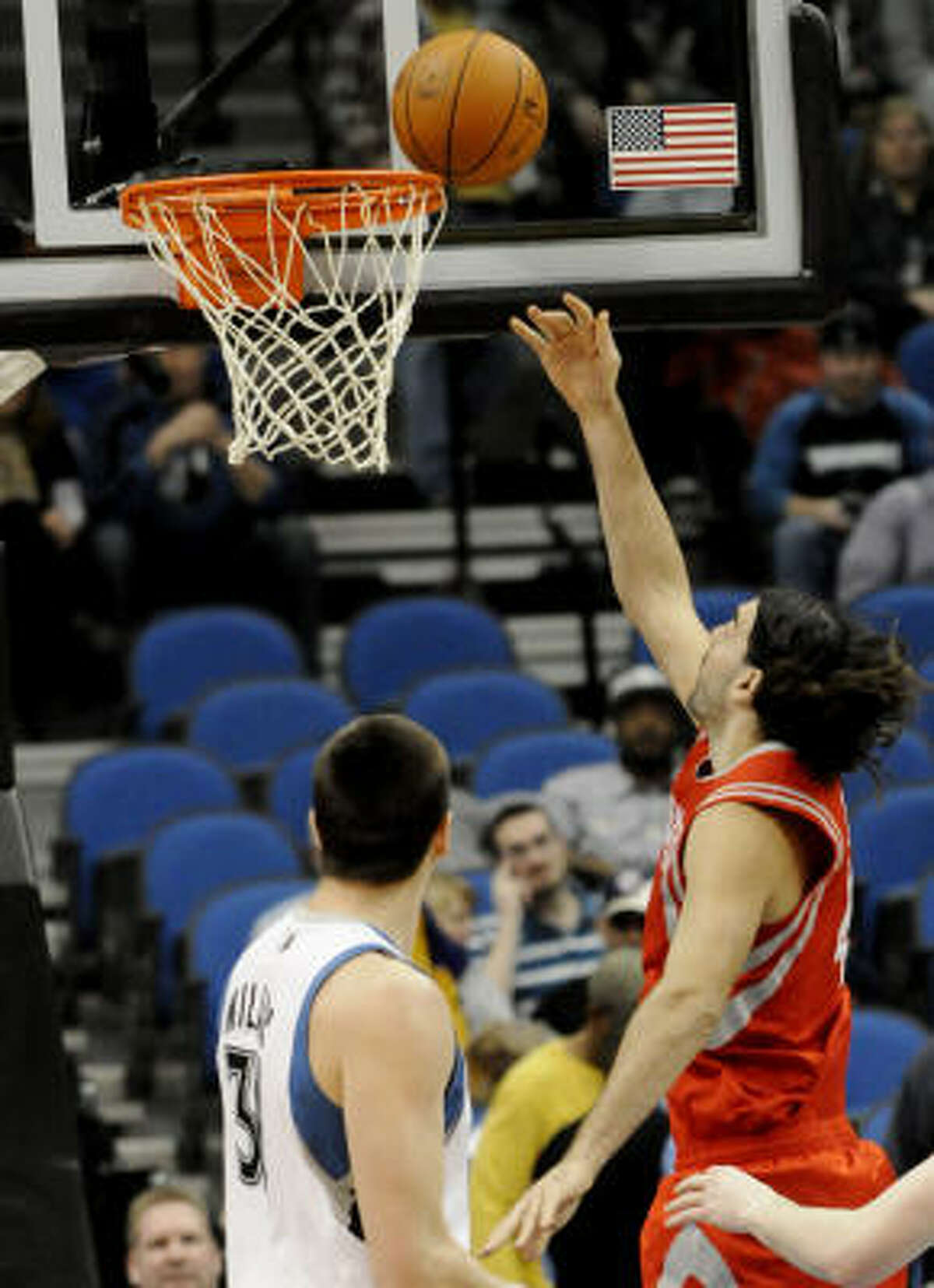 Rockets forward Luis Scola lays the ball up for a basket as Timberwolves center Darko Milicic watches the play.