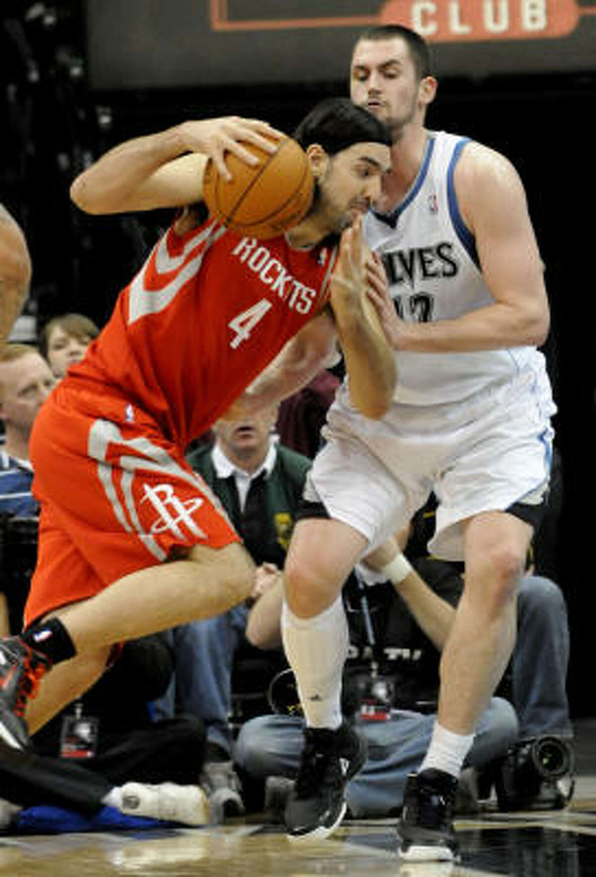 Rockets forward Luis Scola, left, drives around Timberwolves forward Kevin Love.