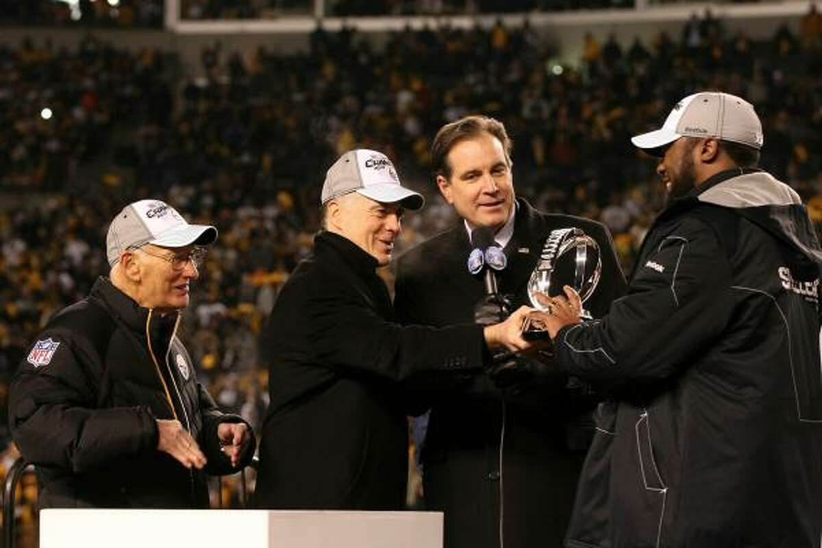 Steelers owner Dan Rooney, left, team president Art Rooney II, second from left, and coach Mike Tomlin, right, of receive the Lamar Hunt Trophy as CBS sportscaster Jim Nantz looks on after Pittsburgh's win over the New York Jets in the AFC championship game Saturday in Pittsburgh. The Steelers advanced to their third Super Bowl in six seasons and will face the Packers.