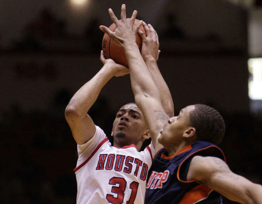 Jan. 22: UTEP 57, UH 52UH guard Adam Brown hits a shot over UTEP's Gabriel McCulley for three of his game-high 22 points. Photo: Bob Levey, For The Chronicle