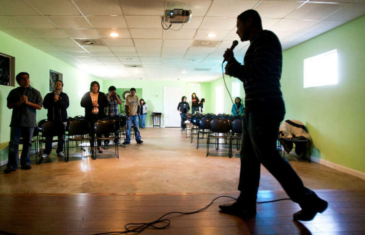 Erik Polio sings during service in Ruta 14:6 church, which was a marijuana grow house for it's past tenants. Church parishioners cleaned up the property and uses it for prayer meetings and activities.