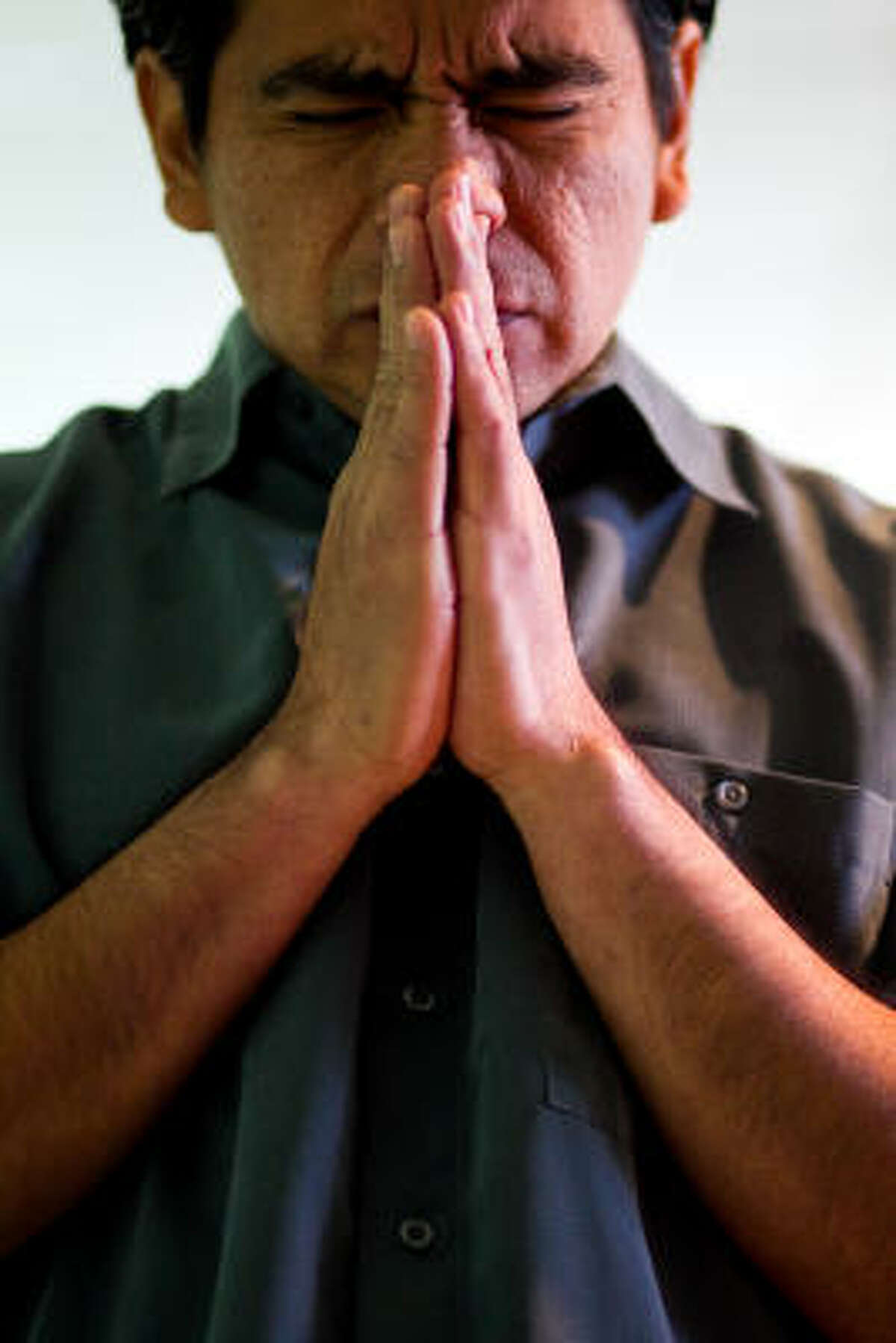 Ruta 14:6 pastor Mauricio Saravia puts his hands together as he listens to a sermon during a service in Houston.