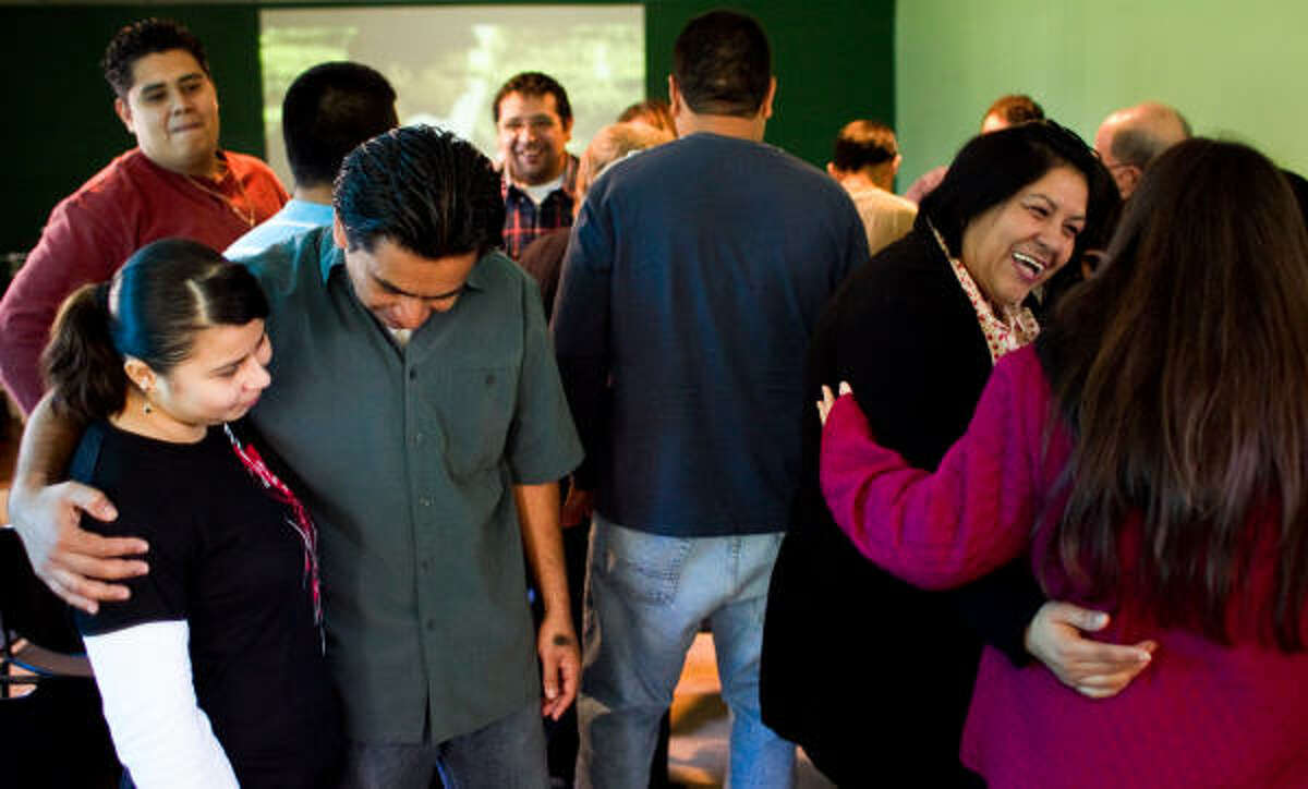 Claudia Ramirez, left, gets a hug from Ruta 14:6 pastor Mauricio Saravia as church service comes to an end in Houston. Ruta 14:6 is housed in what was at one time a marijuana grow house. Church parishioners cleaned up the property and uses it for prayer meetings and activities.
