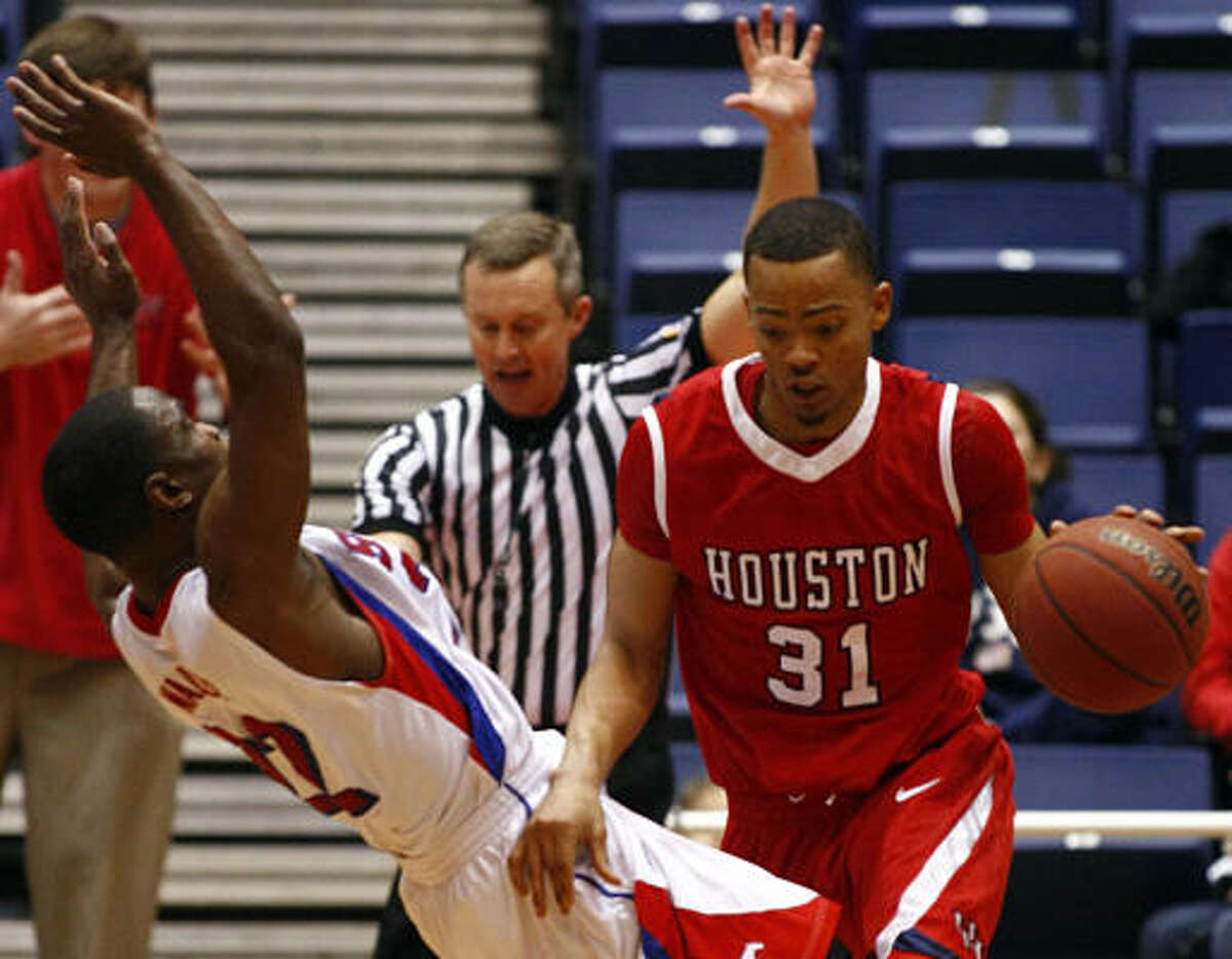 SMU guard Mike Walker, left, draws a charging foul from UH guard Adam Brown in the second half of Saturday's game at Moody Coliseum in Dallas. Brown scored 22 points to help UH escape with a win.