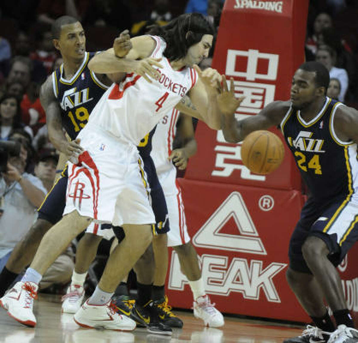 Rockets forward Luis Scola (4) loses the ball to Jazz forward Paul Millsap (24) with help from Raja Bell (19).