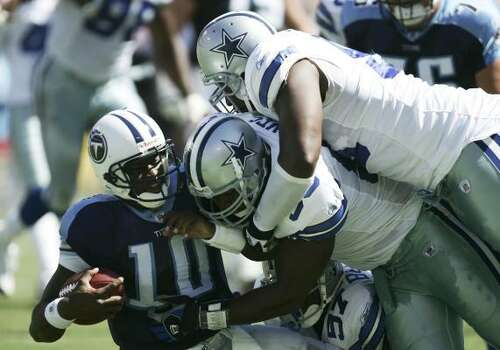 2006 Vince Young took over for the current starter, Kerry Collins, against the Cowboys on Oct. 1. He was 14-of-29 for 155 yards and a touchdown in a 45-14 loss to Dallas at LP Field. He also threw two interceptions and was sacked twice, including this one by Bradie James, center, and Marcus Spears in the second quarter. Photo: Harry How, Getty Images