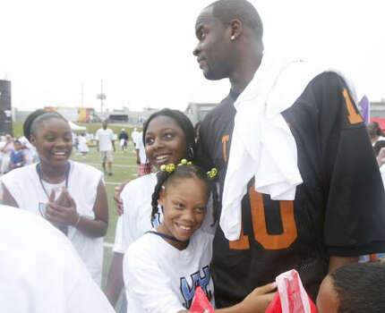 2007 Vince Young came back to Houston, this time wearing his old Texas jersey, to hold the Vince Young Foundation's ''VY 4 Kids Day'' at Butler Stadium on July 14. Here he greets Justus Bonner, second from right, Jade Butler, center, and Christina Homan. Photo: James Nielsen, Chronicle