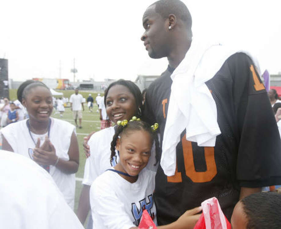 2007Vince Young came back to Houston, this time wearing his old Texas jersey, to hold the Vince Young Foundation's ''VY 4 Kids Day'' at Butler Stadium on July 14. Here he greets Justus Bonner, second from right, Jade Butler, center, and Christina Homan. Photo: James Nielsen, Chronicle