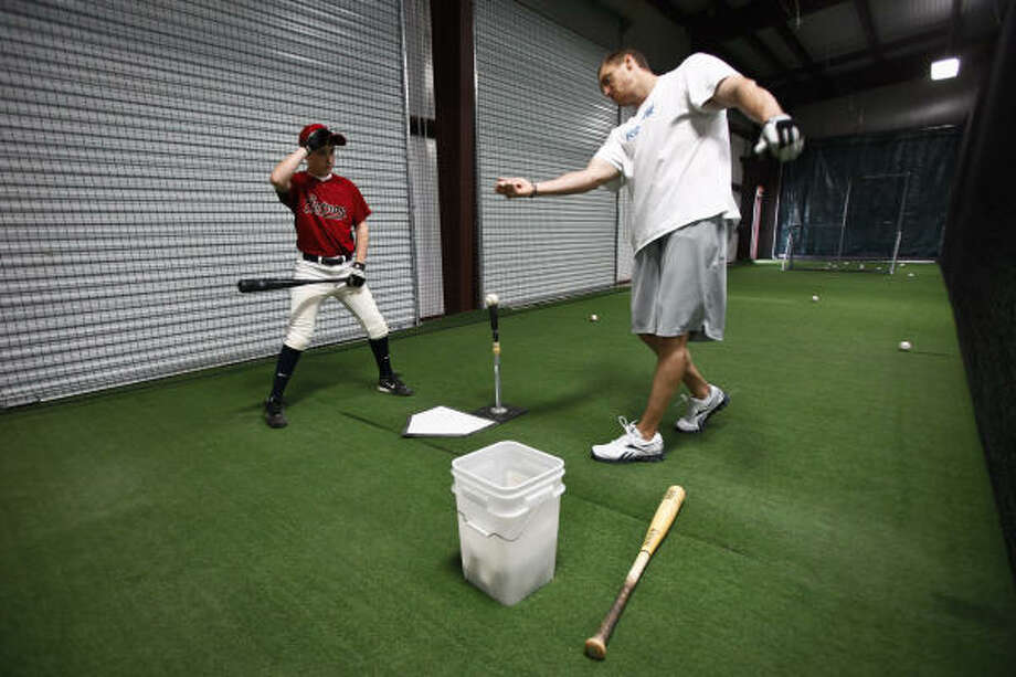 Hunter Pence gives advice to Cameron Carlin, 12, as he hits baseballs off the batting tee. Photo: Michael Paulsen, Chronicle