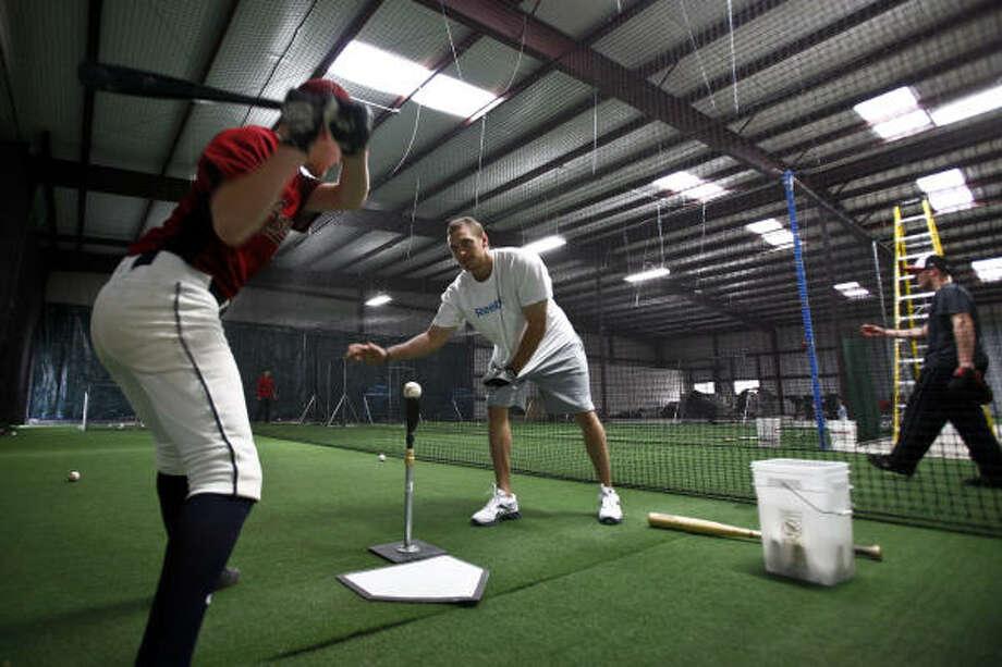 Hunter Pence gives advice to Cameron Carlin, 12, as he hits baseballs off the batting tee. Photo: Michael Paulsen, Chronicle