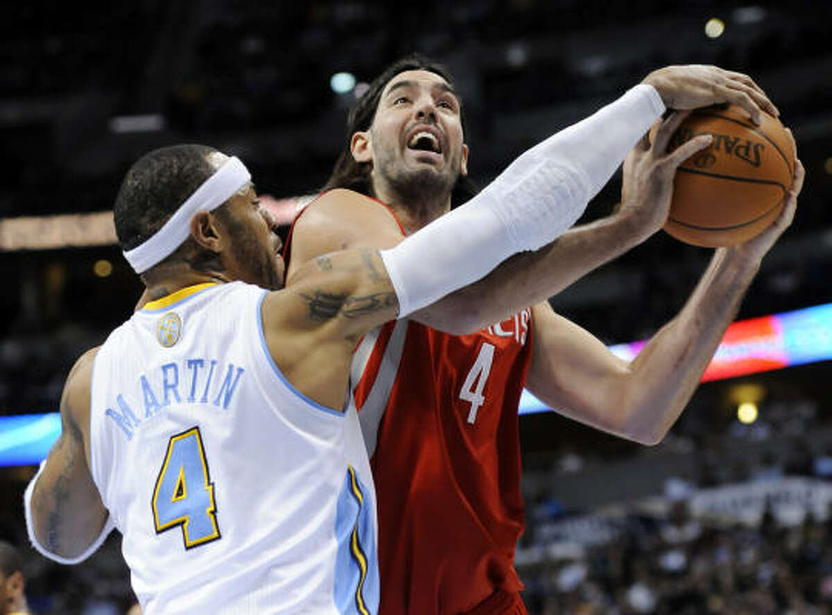 Rockets forward Luis Scola (4) is fouled by Nuggets forward Kenyon Martin (4).